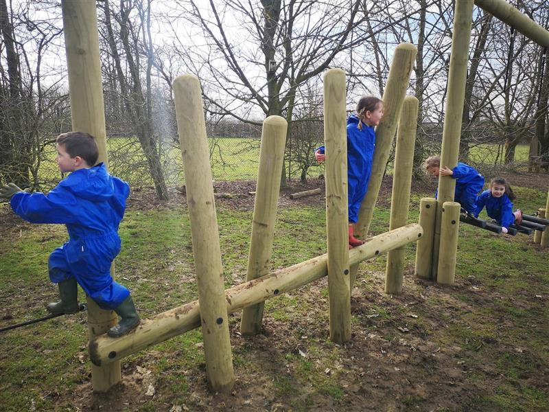 Four children playing and laughing on our log balance weaver with horizontal beam and horizontal log bridge crossing