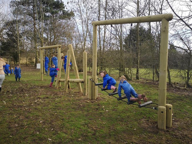 Children playing on a forest trim trail, including a drop rope tightrope, horizontal log bridge and balance weaver with incline beam.