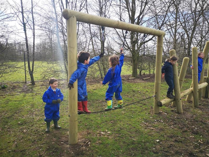 Two children playing on the drop rope tightrope and two children playing on the log balance weaver with horizontal beam.