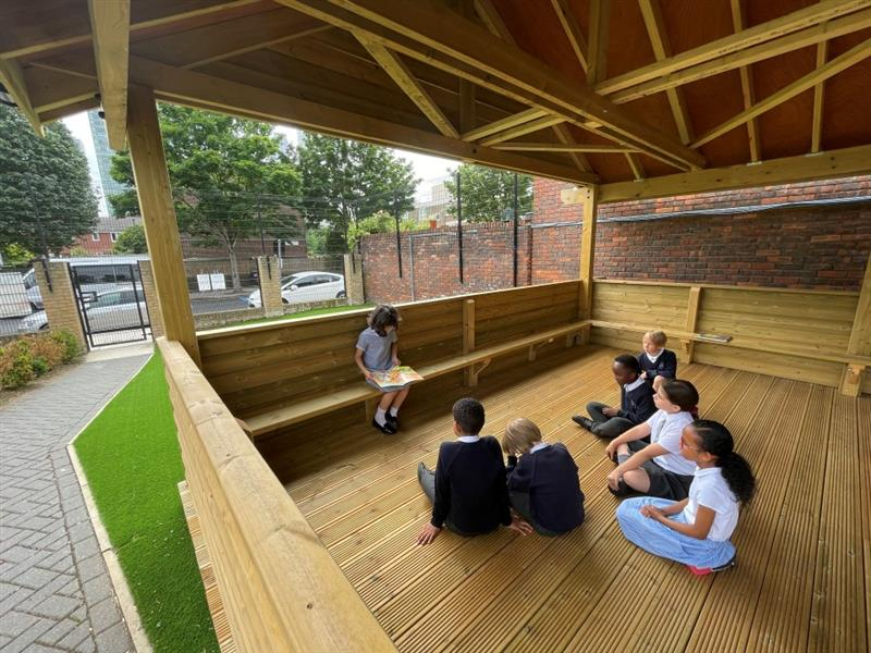 children enjoying story time in the outdoor classroom