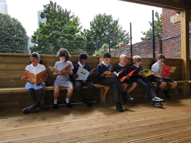 children reading in the outdoor classroom