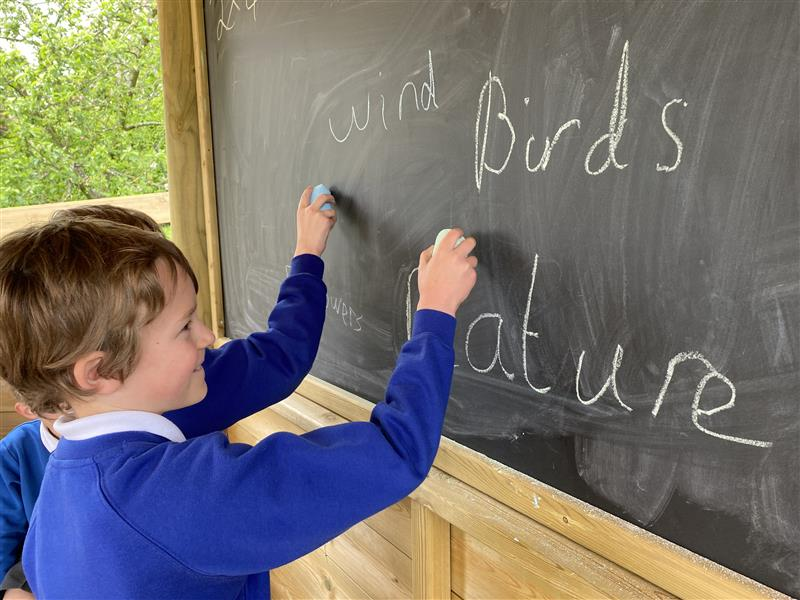 a young boy writing on the chalk board in the gazebo