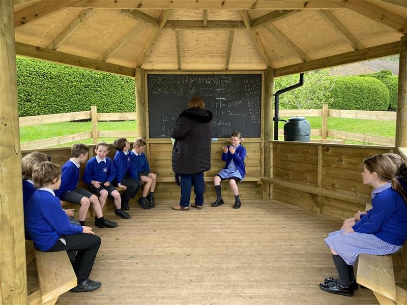 children sat around the edges of the gazebo and the teacher is writing on the chalk board