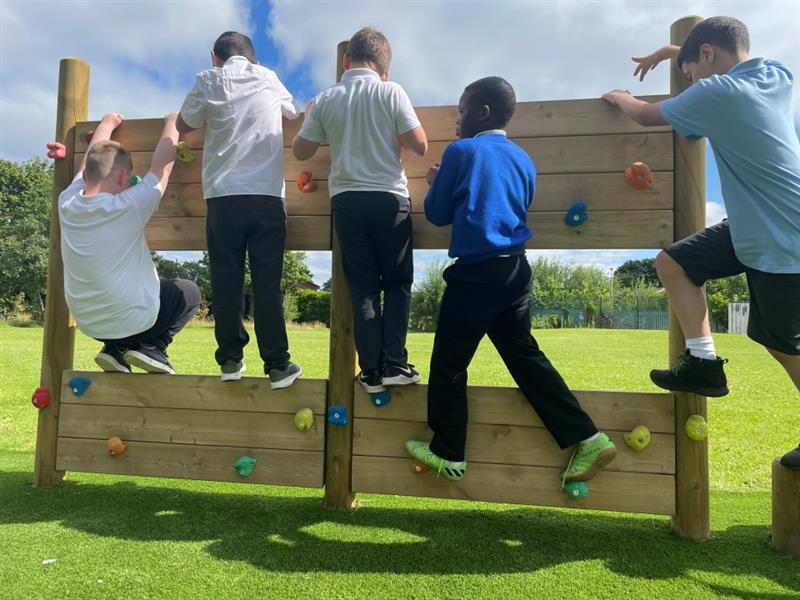 Five children hanging from a climbing wall which is part of their new trim trail