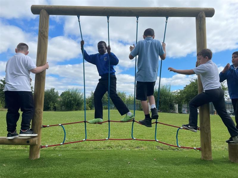 5 children playing on the ropes on their new trim trial, 2 children are in the middle of this apparatus, 1 child is climbing off the end.