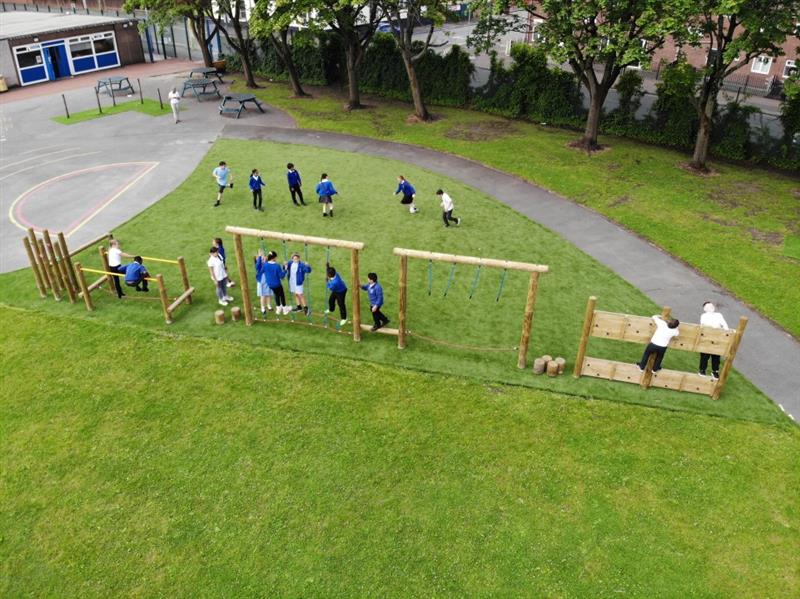 A birds eye view of 15 children playing on a Pentagon Play trim trail with 6 people that is surrounded by artificial grass.