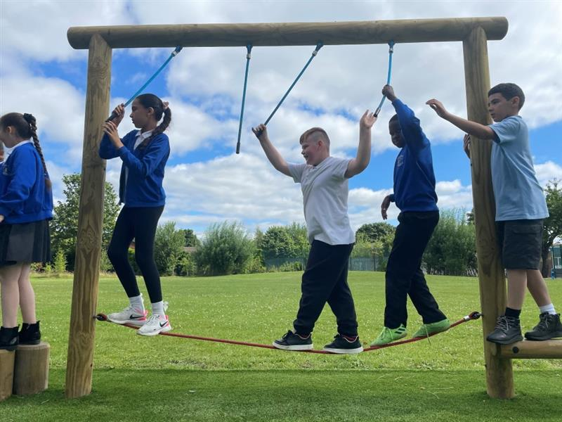 5 children playing on the ropes on their new trim trail.3 children are half way through the apparatus, 1 young girl is getting of and 1 young boy is climbing on to the apparatus.