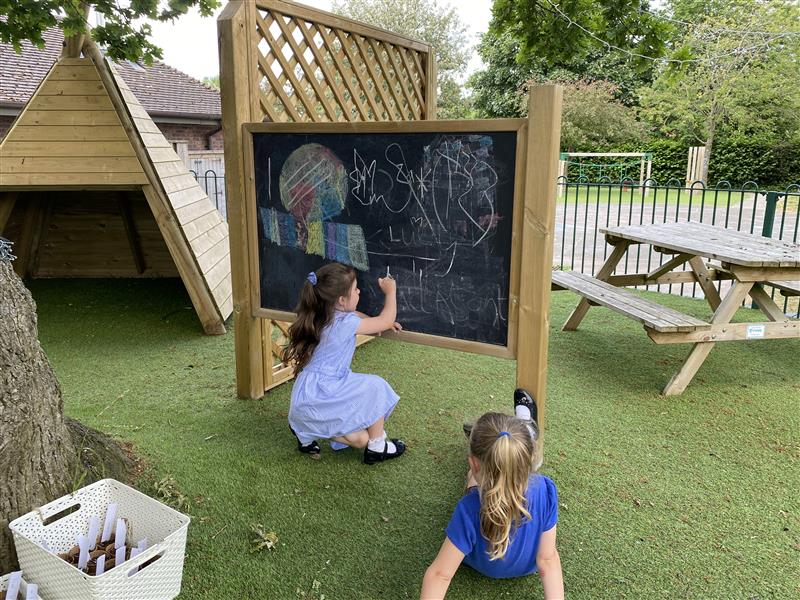 a girld drawing on the chalk board