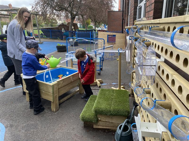 children playing on the waterwall and messy play area