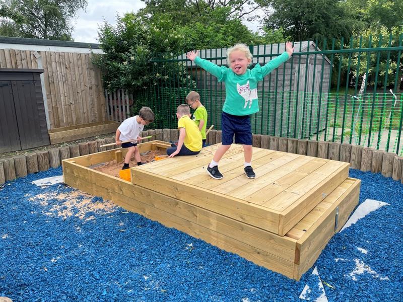 Children playing in sliding sandpit
