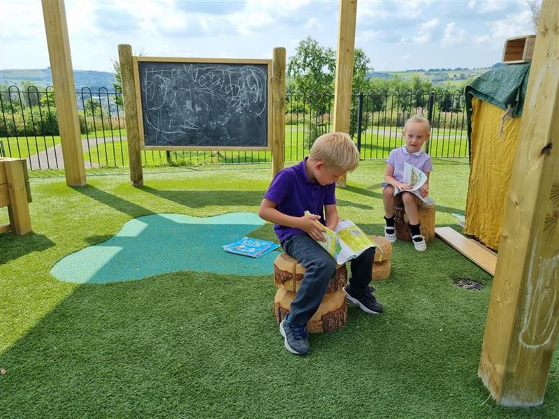 two children reading books sat on the grass top seats