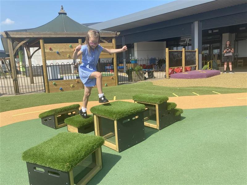 a young girl playing on the get set go blocks at her school, she is stepping up onto a higher block
