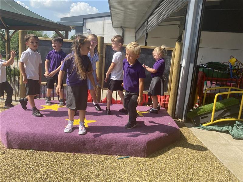 A class of children playing and dancing on their performance stage, the stage is purple and has chalk boards behind.
