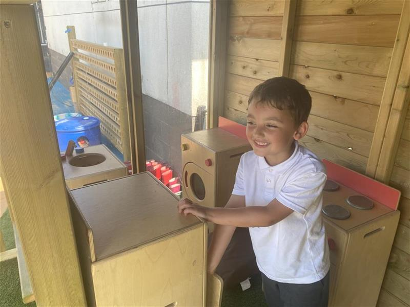 A young boy playing with a kitchen in his lookout cabin