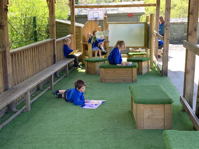 A language and communication zone featuring playground surfacing, seating and mark making panels