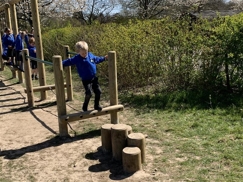 Child tackling the tight rope bridge at the end of a trim trail installed into a park