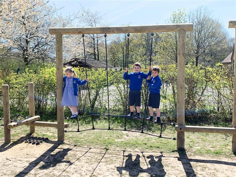3 children hanging on a rope swing traverse as part of a trim trail challenge