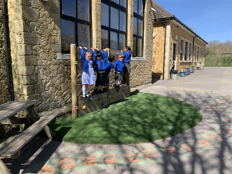 A climbing wall installed against a school building with playturf artificial grass underneath