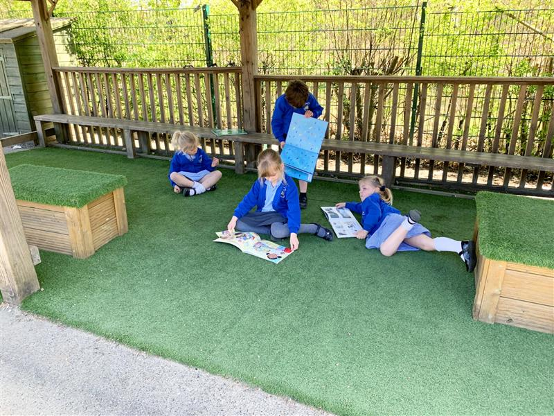 4 children lay on artificial grass reading stories