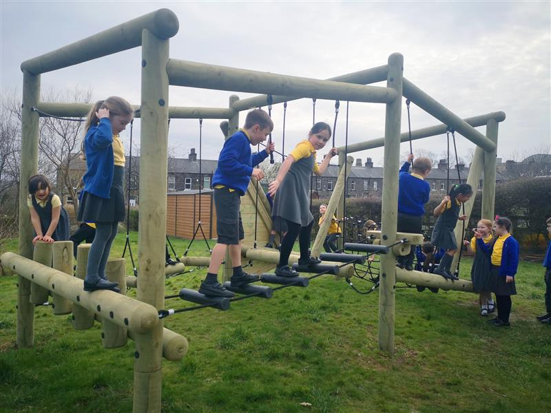 a group of primary school children playing on a puzzlewood forest circuit
