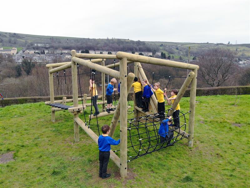 A group of primary school children playing on a school playground climbing frame