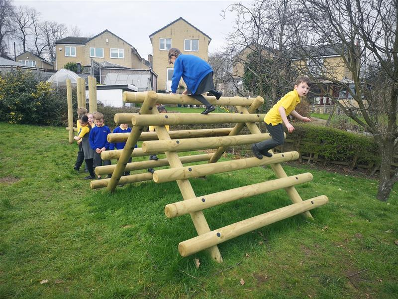 2 children climbing up a log climber and jumping off the beams onto the natural grass