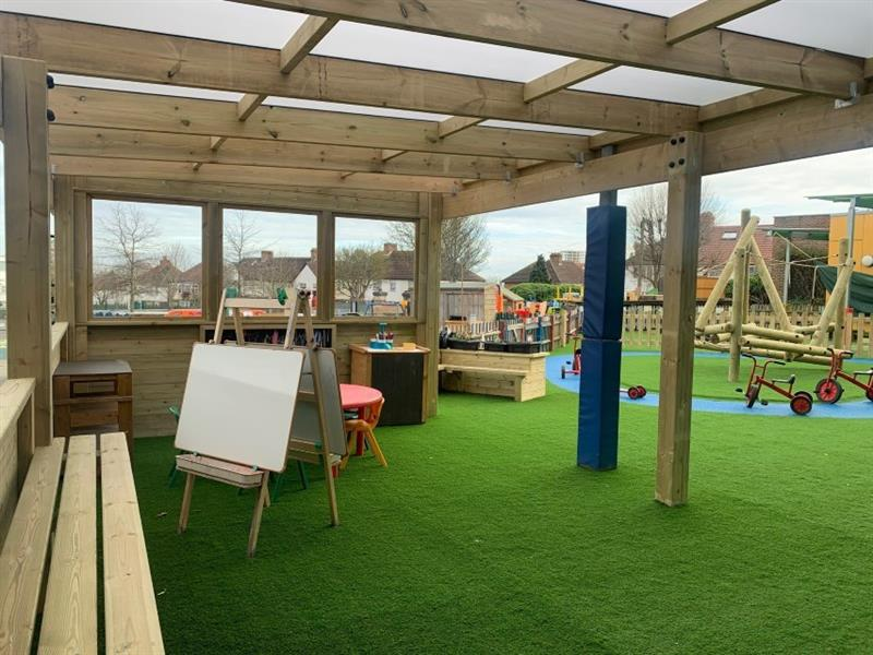 Artificial grass has been installed underneath the timber canopy with benches around the side of the canopy. There is also a whiteboard, chalkboard and tables underneath the canopy.