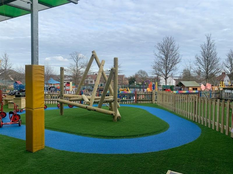 Harter fell climbing frame installed onto artificial grass in front of bow top timber fencing around the edge of the playground. There is yellow padding around one of the metal posts which is attached to the school building.