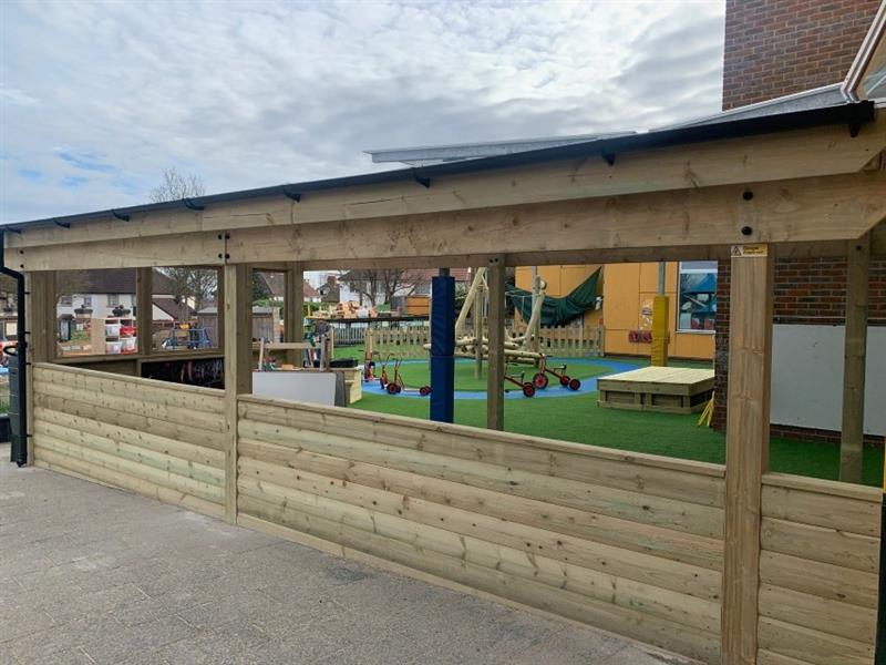 A timber canopy has been installed onto the side of the school building with artificial grass installed inside for a place to children to learn and play inside. There is a whiteboard and chalkboard inside the canopy.