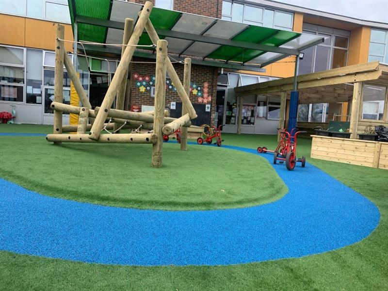 Harter Fell climbing frame has been installed onto artificial grass in front of the school building which has a roadway made out of bright blue safe turf circling the climbing frame with 3 trikes placed onto it.