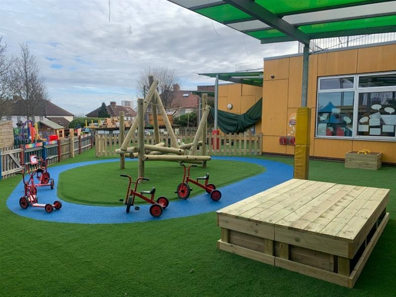Harter fell climbing frame has been installed onto artificial grass in the middle of the playground in front of the school building, with a roadway made out of blue safeturf circling the climbing frame. There are 3 trikes and 1 scooter placed on the roadway.