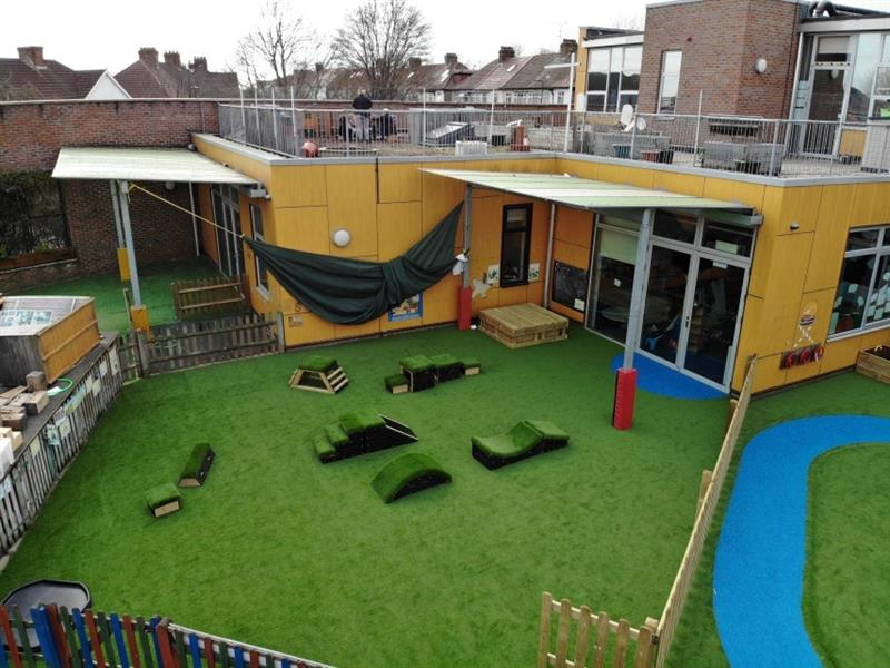 Aerial view of EYFS playground which has artificial grass, a large sandbox and get set, go! blocks placed on the artificial grass. The playground is next to the yellow school building which has a rooftop area.
