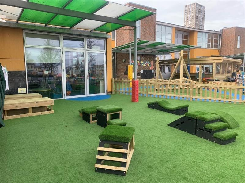EYFS playground which includes get set, go! blocks, a large sand box, a climbing frame and a roadway which has all been installed onto artificial grass in front of the school building.