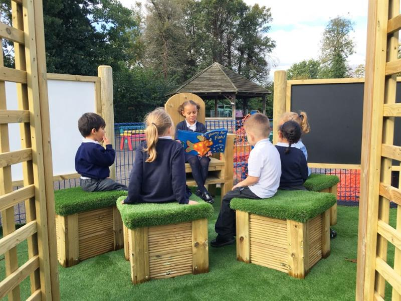 a child sitting on a storytelling chair reading out loud to 5 children sat on artificial grass topped seats