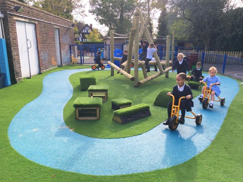 A climbing frame and set of get set go blocks on artificial grass surrounded by a blue wetpour river