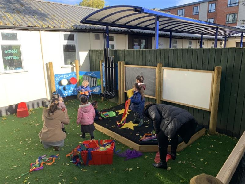 Toddlers playing on a outdoor performance stage