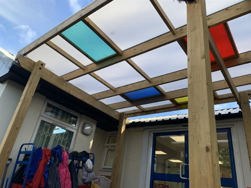 A timber canopy with coloured roof panels installed into a nursery garden