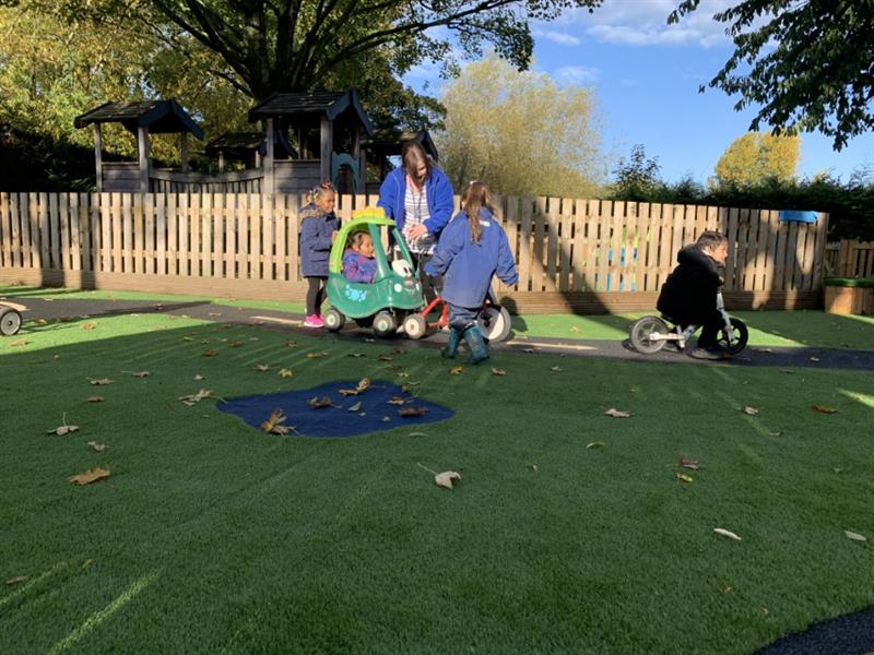 Toddlers riding trikes around a wetpour surfacing track