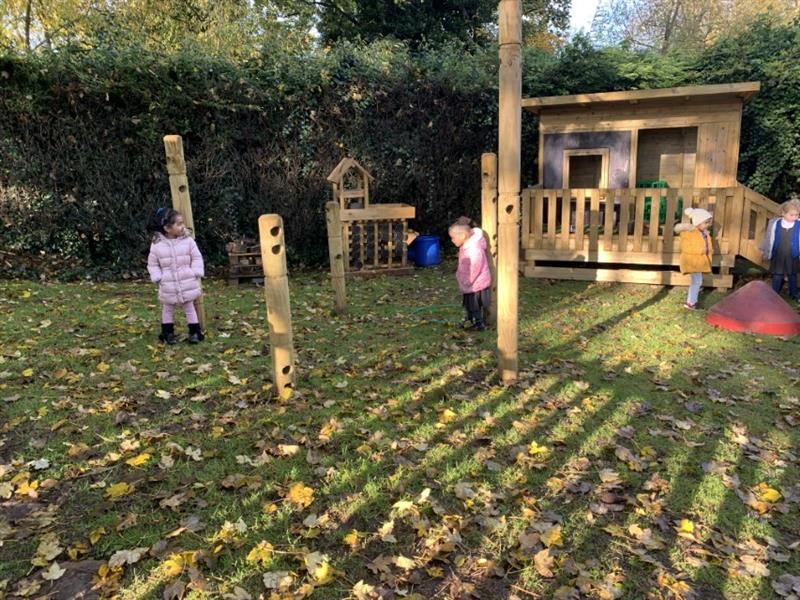 Toddlers playing with den making equipment in their nursery garden