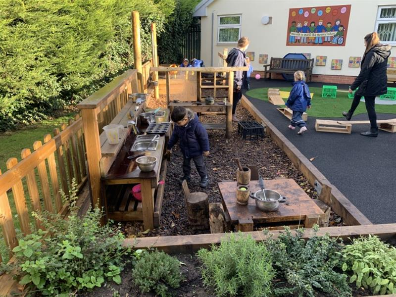 Toddlers playing with outdoor play equipment in their nursery garden
