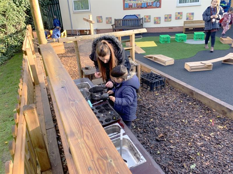 A child and nursery practitioner playing with an outdoor mud kitchen