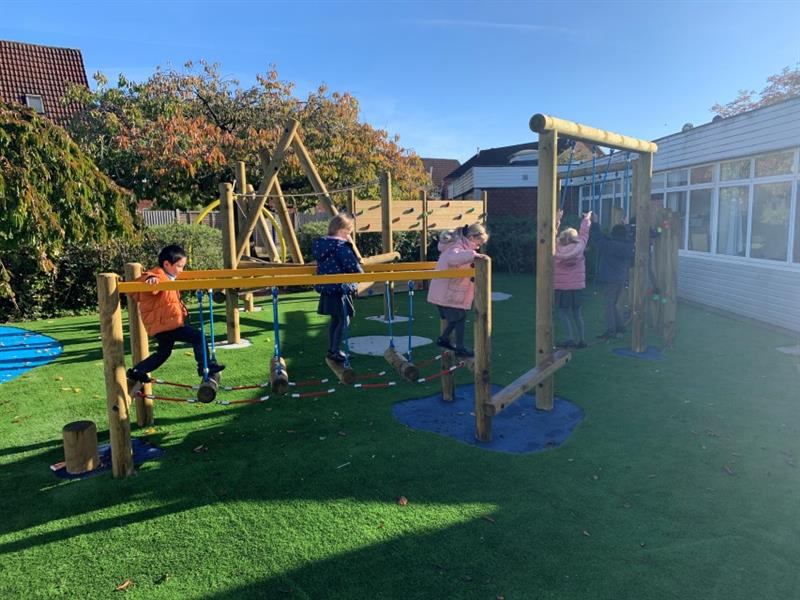 6 children playing on trim trail equipment which has been installed in front of the school building with one child wearing an orange coat, 3 children wearing navy blue coats and 2 children wearing pink coats.