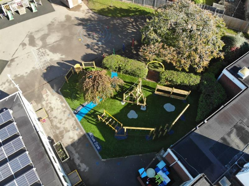 Aerial view of the playground which includes trim trail equipment and the communication and language zone which is separated by a large tree and blue safeturf designed in the shape of a river with quiet zone and active zone written in each area.