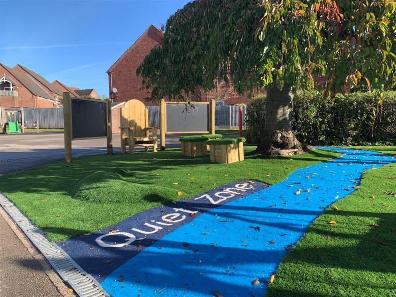 A photo of the communication and language zone which has been placed next to a large tree with one surface mound and blue safeturf to create a river with 'Quiet Zone' written next to the river.
