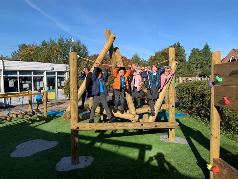 6 children smiling at the camera playing on the harter fell climber which has been installed onto artificial grass next to trim trail equipment, with one child wearing a blue jumper running past the school building.