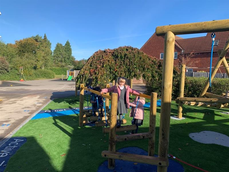 2 children playing on a wobbly bridge at the start of the trim trail equipment with one child in a pink coat stood next to the wobbly bridge watching. The play equipment has been installed onto artificial grass.