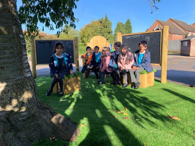 7 children sat in the communication and language zone which includes seats topped with artificial grass, a storytelling chair and 2 chalkboards which have been placed next to a large tree.