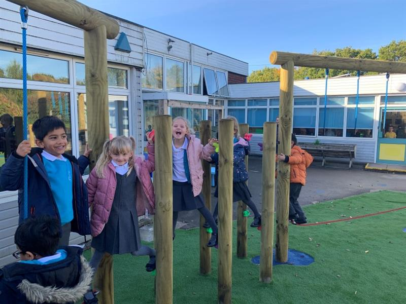 6 children smiling, playing on forest climbing poles and trim trail equipment which has been installed onto artificial grass in front of the school building.