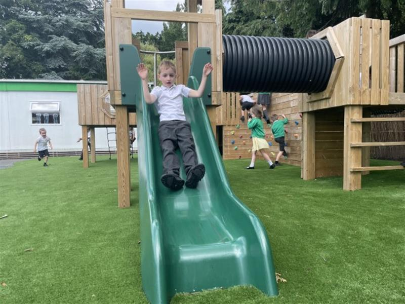 a child in school uniform sliding down a slide