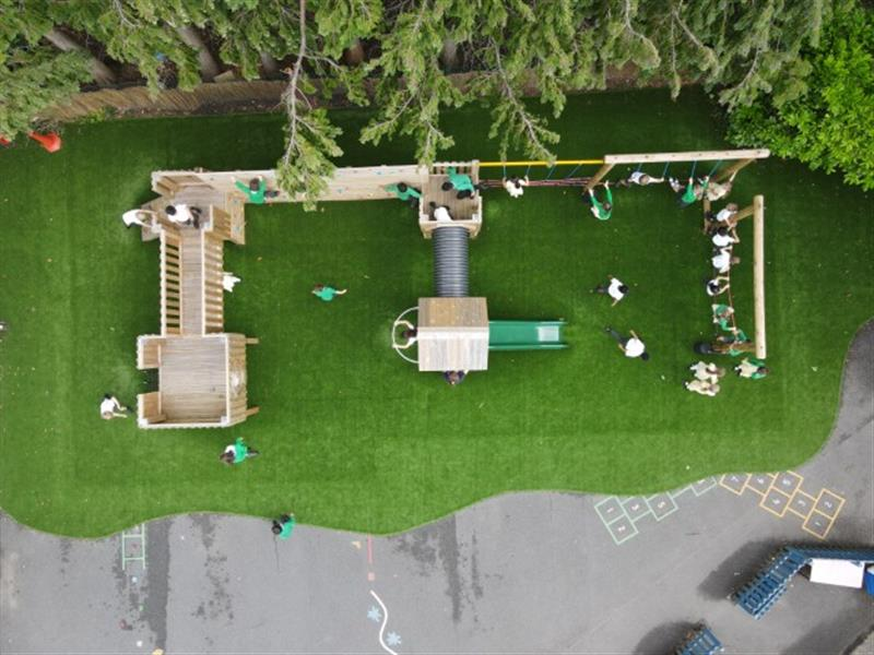 An overhead view of a playground tower installed onto artificial grass